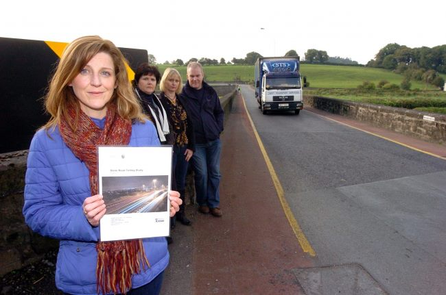 Campaigners hold one of the many Traffic Management Reports compiled for Slane village as an HGV traverses Slane Bridge. Photo Credit: Seamus Farrelly.
